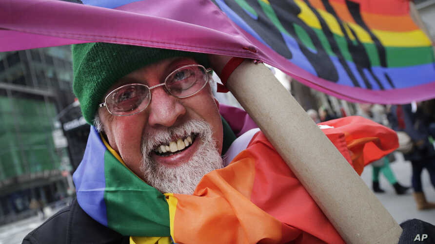 """FILE - Artist Gilbert Baker, designer of the Rainbow Flag, is draped with the flag while holding a banner that reads """"Boycott Homophobia"""" before the start of the St. Patrick's Day parade in New York City, March 17, 2014."""