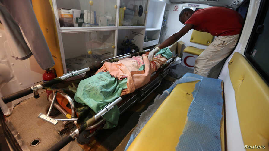 A medic places the body of a woman in an ambulance after she was killed by clashes between government forces and Houthi fighters near Hodeida, Yemen June 15, 2018.
