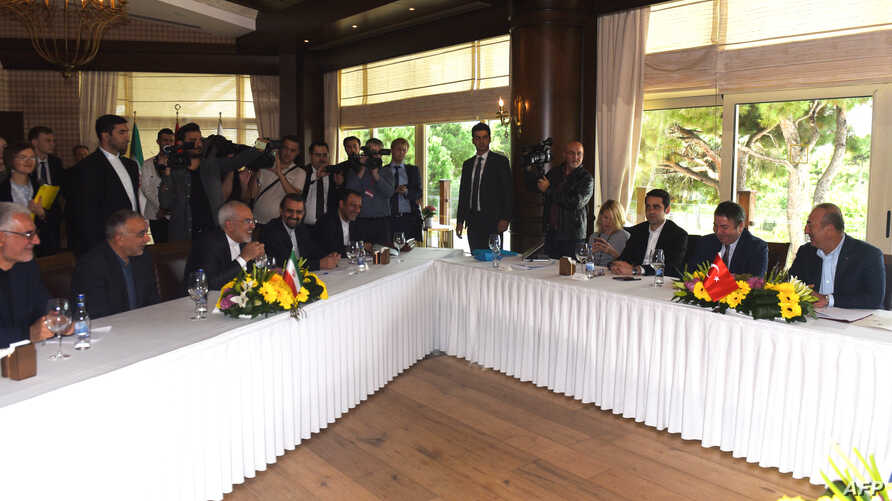 Iranian FM Mohammad Javad Zarif (3L) and Turkish FM Mevlut Cavusoglu (R) attend a meeting in Antalya on Nov. 19, 2017 as top diplomats from Iran, Russia and Turkey met to discuss the civil war in Syria.