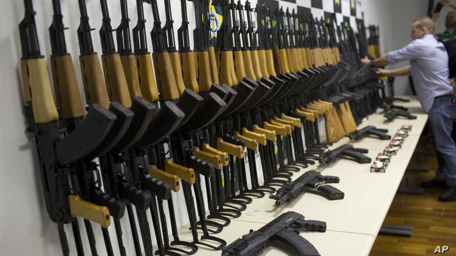 FILE - Police show 60 confiscated automatic rifles during a news conference in Rio de Janeiro, Brazil, June 1, 2017.