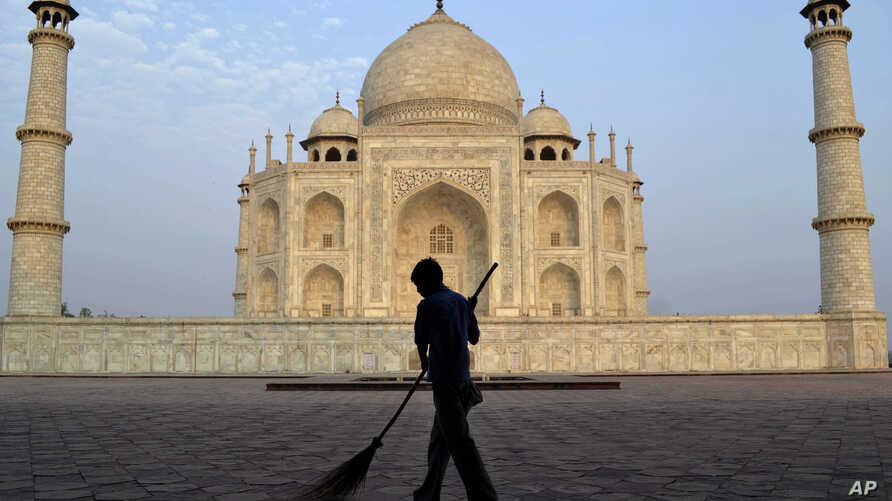 FILE - In this June 3, 2013, photo, a worker sweeps in front of Taj Mahal in Agra, India. India's Supreme Court has ordered a state government to remove a wood-burning crematorium from near the Taj Mahal to protect the iconic monument from pollution