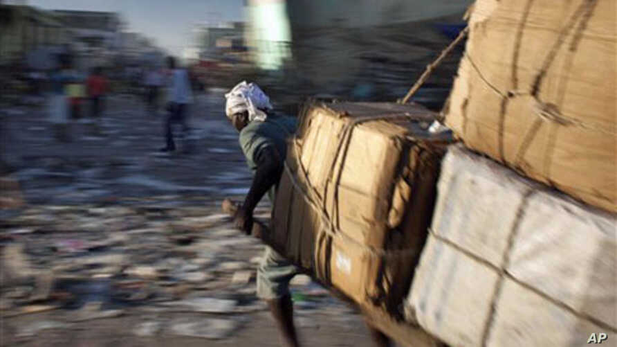 A man pulls a cart with merchandise past quake-damaged buildings in downtown Port-au-Prince, Haiti, 06 Jan 2011