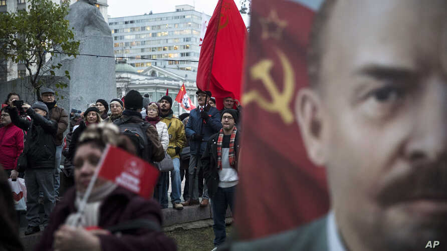 Communist Party supporters stand next to a monument to Karl Marx, left, and hold Soviet flags and portraits of Soviet founder Vladimir Lenin, right, during a demonstration marking the 100th anniversary of the 1917 Bolshevik Revolution in Moscow, Russ