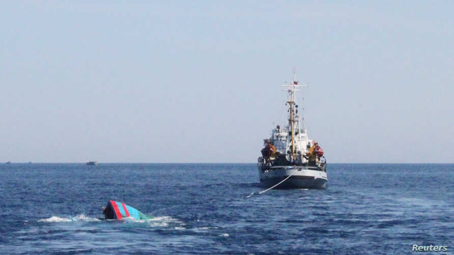 A Vietnamese sinking boat (L) which was rammed and then sunk by Chinese vessels near disputed Paracels Islands, is seen near a Marine Guard ship (R) at Ly Son island of Vietnam's central Quang Ngai province May 29, 2014.