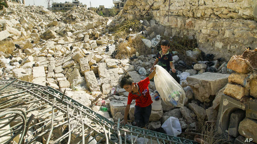 Young boys collect cans in ruins in Aleppo, Syria, Sept. 12, 2017.