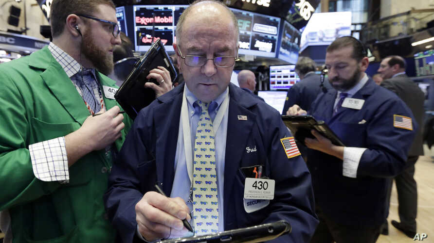 Frederick Reimer, center, works with fellow traders on the floor of the New York Stock Exchange, Jan. 27, 2017.