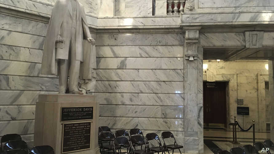 FILE - This July 20, 2017 file photo shows a statue of Jefferson Davis in the Kentucky Capitol in Frankfort, Ky.  State officials are set to give an update on plans to remove a plaque from a statue of Jefferson Davis declaring him to be a patriot and