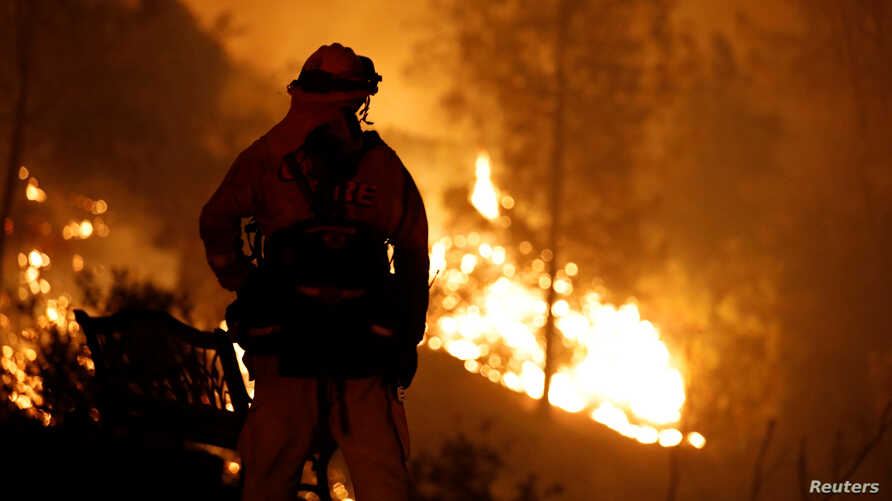 A firefighter watches flames advance up a hill toward homes as crews battle the Carr Fire, west of Redding, California, July 27, 2018.