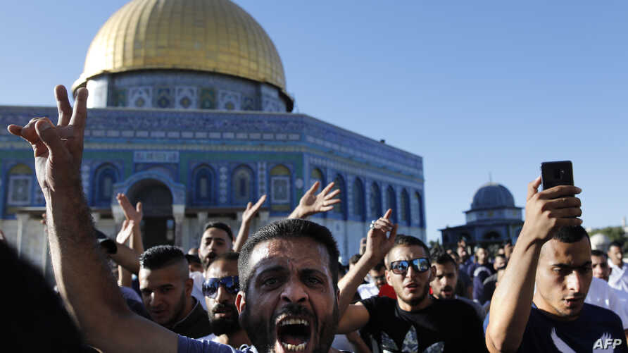 Palestinians shout slogans in front of the Dome of the Rock at the al-Aqsa mosque compound in the Jerusalem's Old City after the site was reopened, July 27, 2018.