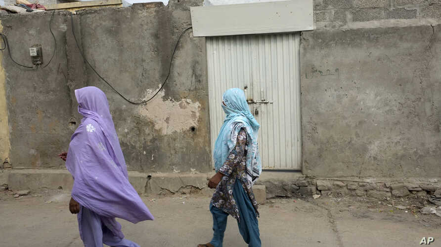 Local women walk past the locked house of a Christian girl in a suburb of Islamabad, Pakistan on Aug. 20, 2012. Pakistani authorities arrested a Christian girl and are investigating whether she violated the country's strict blasphemy laws.