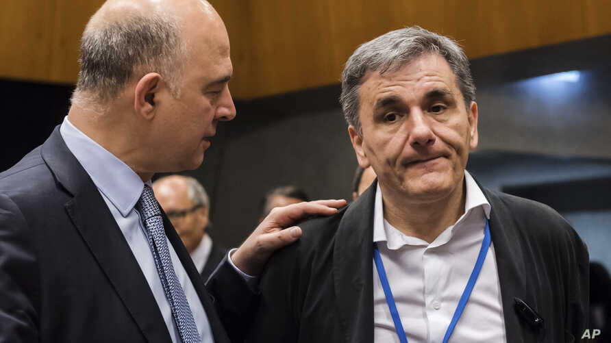 European Commissioner for Economy Pierre Moscovici, left, speaks with Greek Finance Minister Euclid Tsakalotos during a meeting of eurogroup finance ministers at the European Council building in Luxembourg, June 15, 2017.