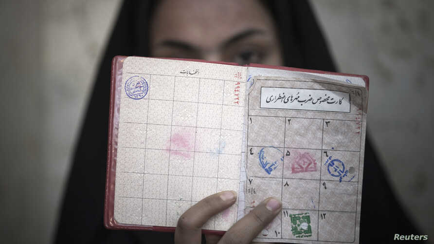 A woman holds her identification in front of her face after voting at a polling station during Iran's parliamentary election in southern Tehran, March 2, 2012.