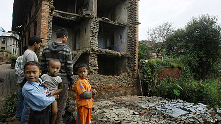 Nepalese children and other people stand near the debris of collapsed buildings damaged by an earthquake that shook northeastern India on Sunday night, in Katmandu, Nepal, Sept. 19, 2011.