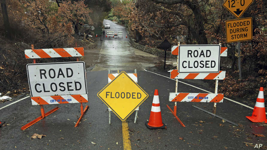 A road is closed because of flooding in an area burned by the Woolsey Fire in Malibu, Calif., Dec. 6, 2018. A second fall storm dumped snow and rain that jammed traffic on Southern California highways and loosened hillsides in wildfire burn areas.