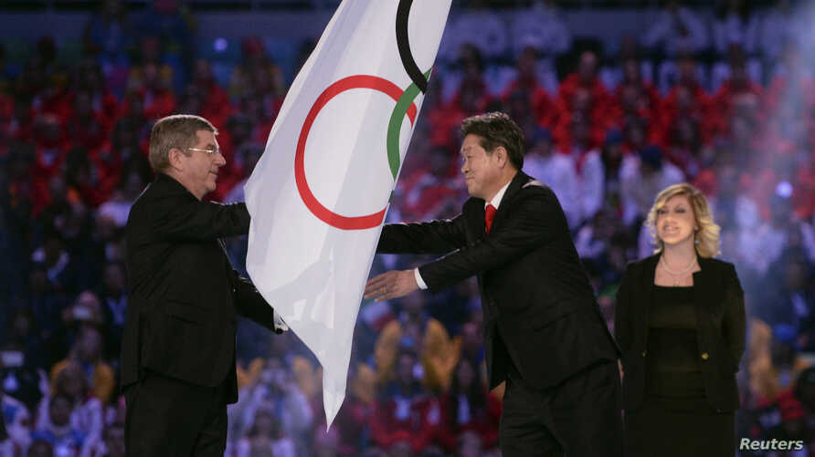 International Olympic Committee (IOC) President Thomas Bach (L) passes the Olympic flag to PyeongChang Mayor Lee Sok-ra (2nd R) during the closing ceremony for the Sochi 2014 Winter Olympics, Feb. 23, 2014.