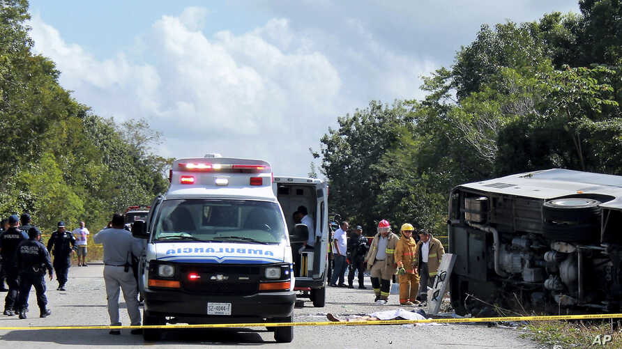 The lifeless body of a passenger lies next to an overturned bus, as ambulances, firefighters and police stand by in Mahahual, Quintana Roo state, Mexico, Tuesday, Dec. 19, 2017.
