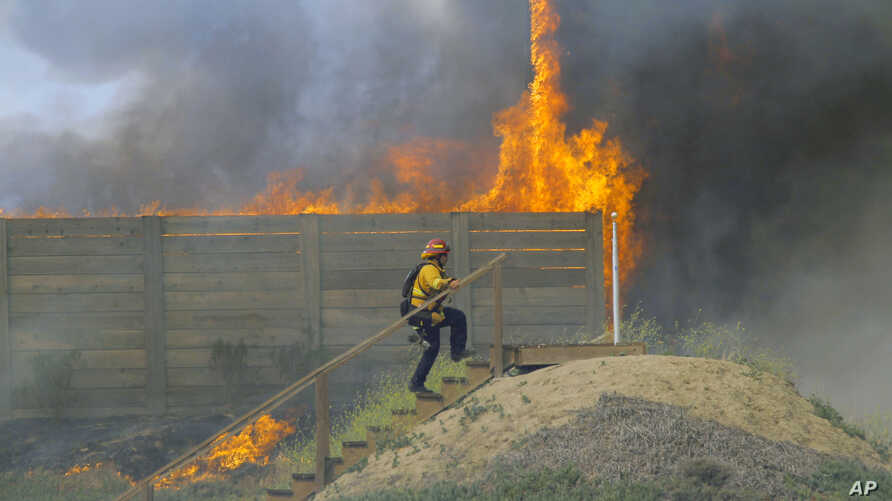 A brush fire burns at a shooting range on the beach at Navel Base Ventura County May 3, 2013
