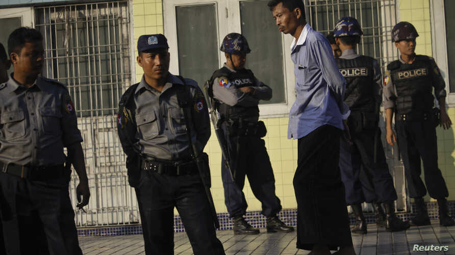 Police stand near Sule pagoda as they guard the city. Just before midnight when the crude time-bomb exploded in the ninth-floor guest room in the luxurious Traders Hotel in Myanmar's biggest city, badly wounding an American tourist and showering the