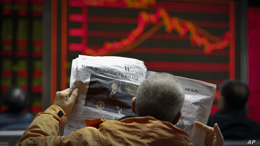 A man reads a newspaper reporting a story of U.S. President Donald Trump opening conditional dialogue with North Korean leader Kim Jong Un, at a brokerage house in Beijing, Jan. 8, 2017. Trade between China and North Korea fell 50 percent in December