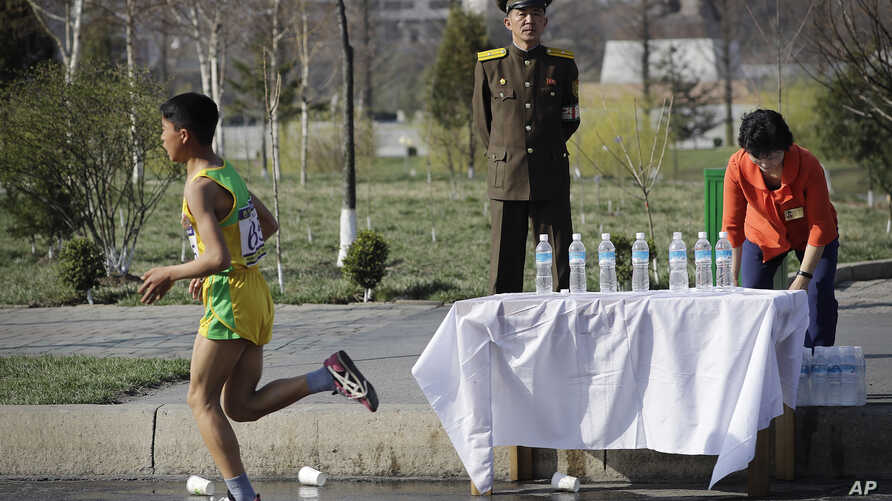 A North Korean military soldier stands on duty while a participant of the Pyongyang marathon runs past a water station, April 9, 2017, in Pyongyang, North Korea. Hundreds of foreigners took to the streets of Pyongyang Sunday for an annual marathon th