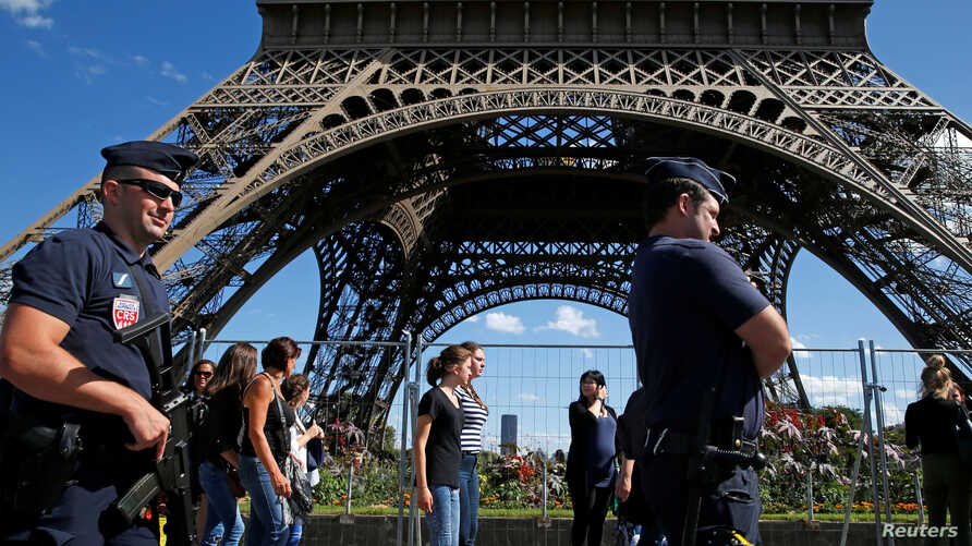 FILE - French CRS policemen patrol as tourists walk past in front of the Eiffel Tower in Paris, Aug. 20, 2016.