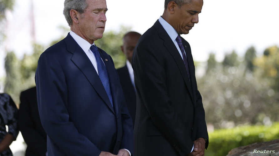 U.S. President Barack Obama and former President George W. Bush (R) attend a memorial for the victims of the 1998 U.S. Embassy bombing in Dar es Salaam, July 2, 2013.