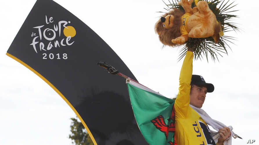 Tour de France winner Geraint Thomas of Wales, wearing the overall leader's yellow jersey, celebrates his Tour de France win with the flag of Wales on the podium on the Champs-Elysees in Paris, France, July 29, 2018.