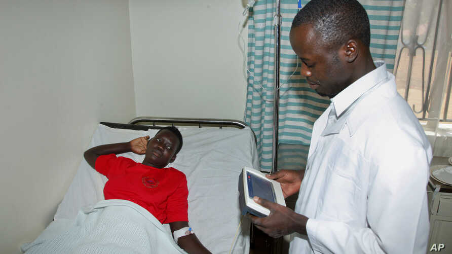 FILE - A doctor talking with a pacient at the Ntinda hospital in Kampala, Uganda.