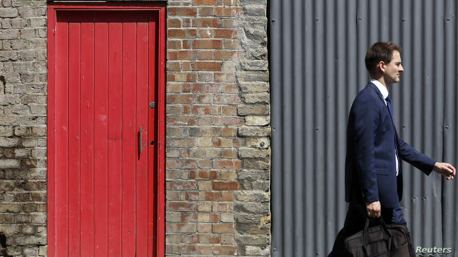 FILE - A man passes a red door and corrugated iron in central London, July 2, 2014.