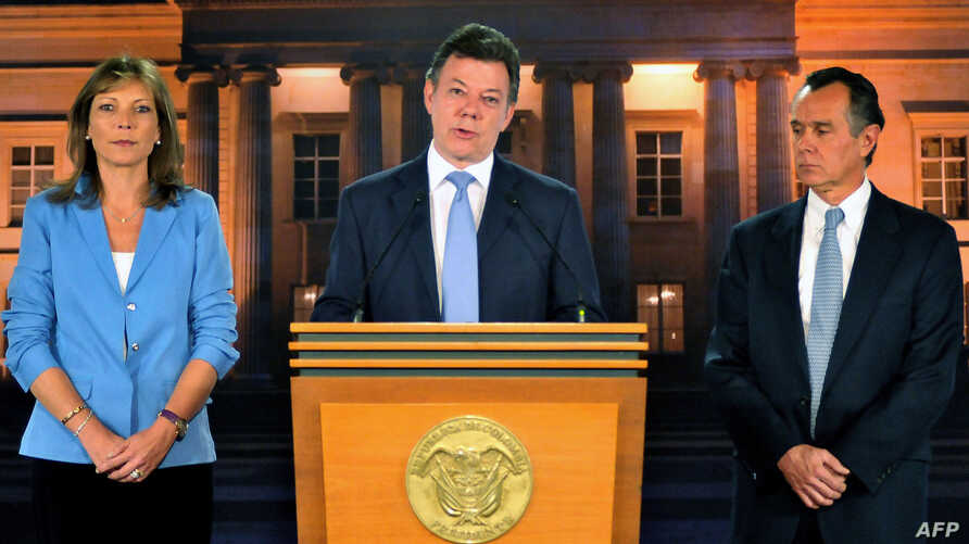 Handout picture released by the Colombian presidency press office showing Colombian President Juan Manuel Santos (C) speaking next to his wife Clemencia de Santos (L) and his doctor Felipe Gomez during a press conference at the Narino Palace, in Bogo