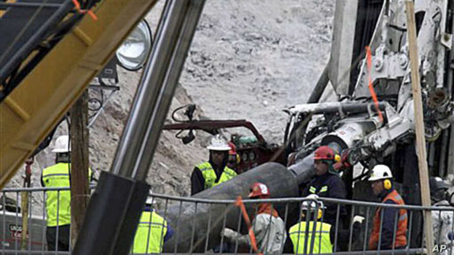 Rescue workers insert steel pipes to encase the escape tunnel that will be used to free trapped miners at the San Jose mine near Copiapo, Chile, 10 Oct 2010