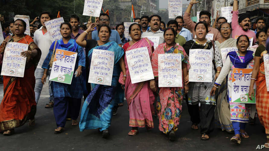 Activists of Trinamool Congress party hold banners and shout slogan during a protest march against the government's decision to withdraw high denomination notes from circulation, in Kolkata, India, Nov. 28, 2016.