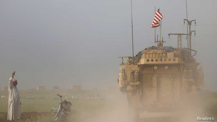 FILE - A man gestures at U.S military vehicles driving in the town of Darbasiya next to the Turkish border, Syria, April 28, 2017.