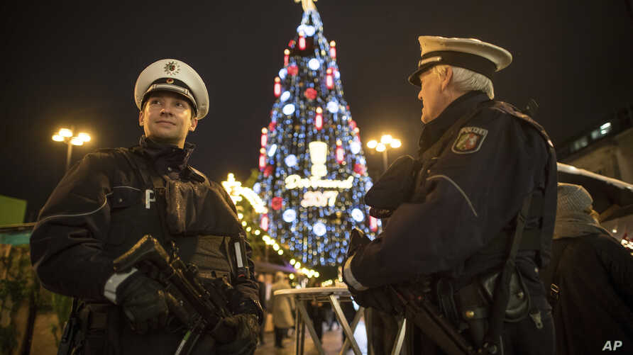 Armed police forces stand in front of the world's largest Christmas tree, according to the organizers, at the Christmas market in Dortmund, Nov. 27, 2017.