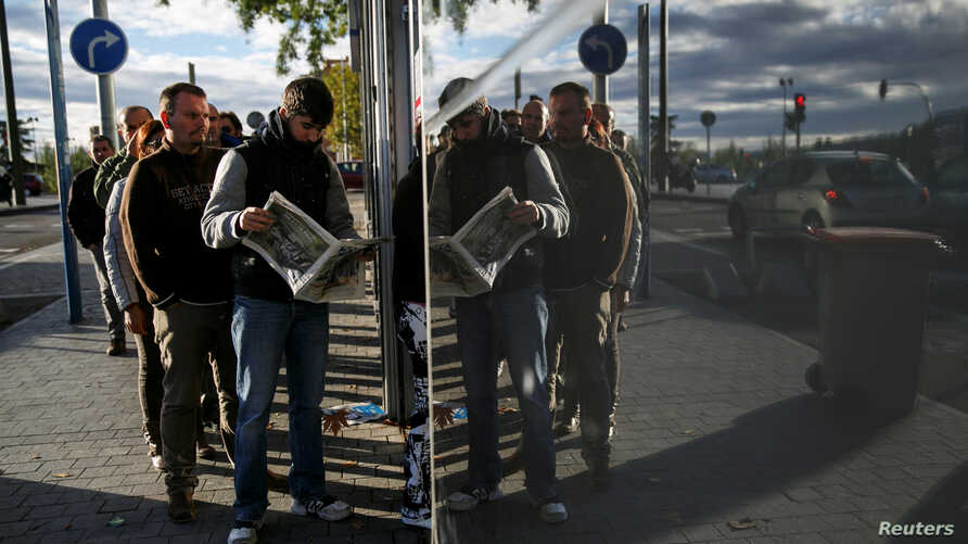 FILE - People wait in line to enter a government-run employment office in Madrid, Nov. 4, 2014.