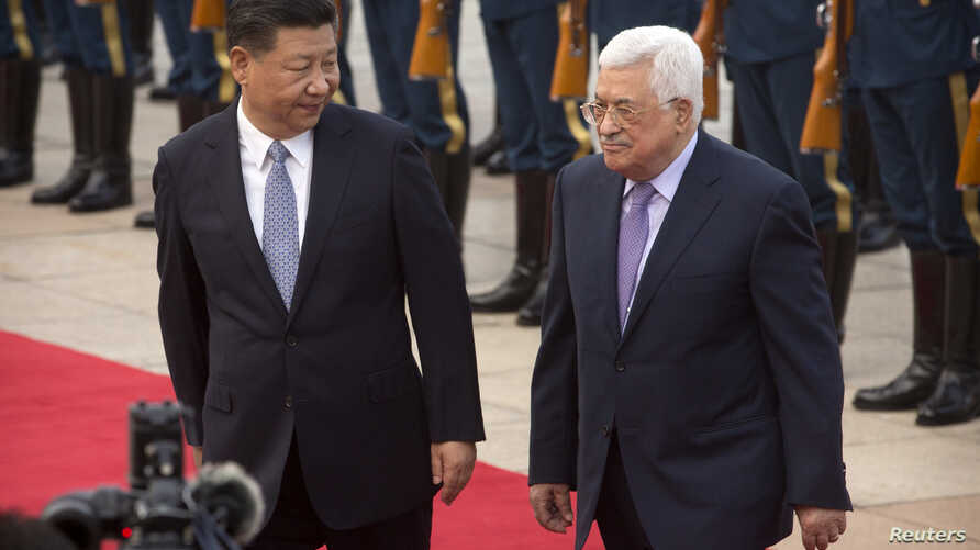 Chinese President Xi Jinping, left, acknowledges Palestinian President Mahmoud Abbas, right, as they walk together during a welcome ceremony at the Great Hall of the People in Beijing, July 18, 2017.