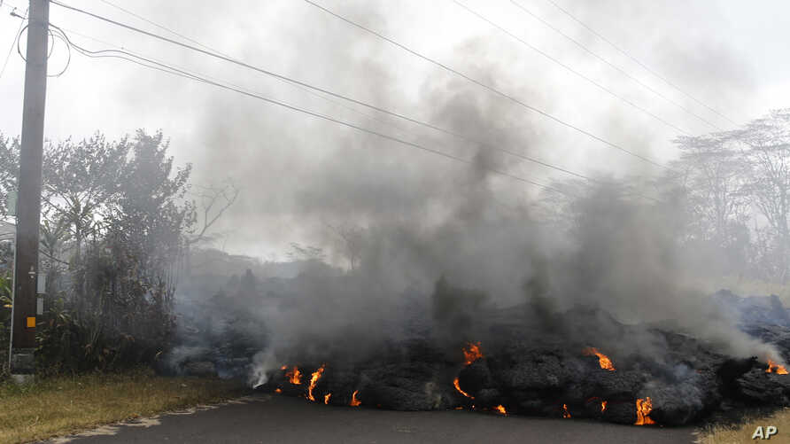 Lava crosses the road near Pohoiki Road, May 18, 2018, near Pahoa, Hawaii. Several open fissure vents are still producing lava splatter and flow in evacuated areas. Gas is also pouring from the vents, cloaking homes and trees in smoke.
