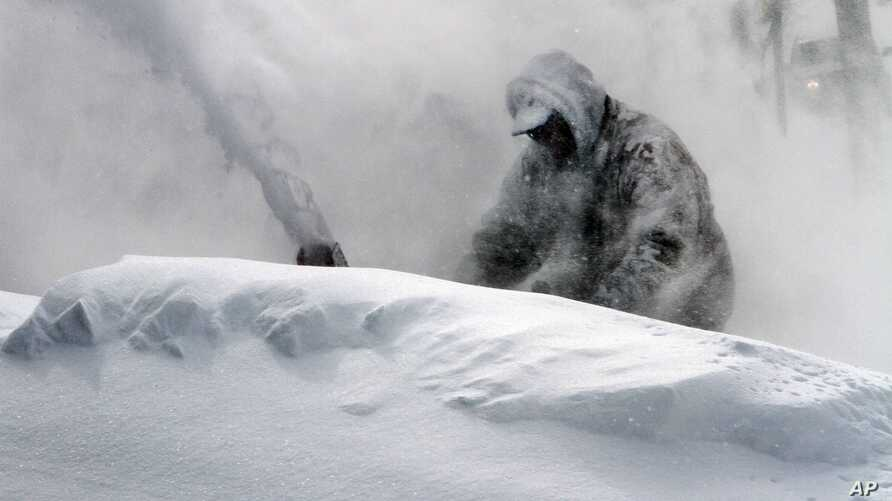 Neil Hodges uses a snow blower to clear drifting snow from in front of his home in Concord, N.H. on Saturday, Feb. 9, 2013.