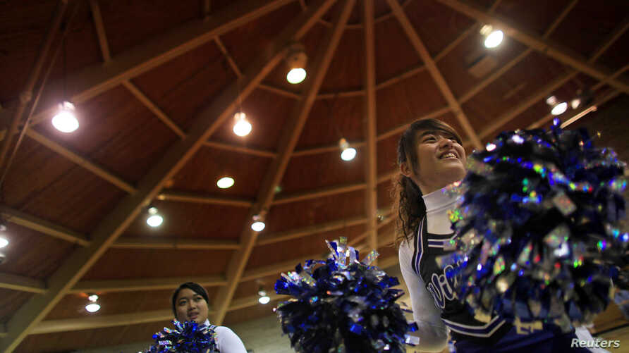 Tina Chuang (R), a foreign exchange student from Pingtung, Taiwan joins her fellow cheer team members Jutarat Sawatpoon (C) from Thailand, and Amy Wang from Shenyang, China, during the introduction of the Grant-Deuel School Girls' Varsity basketball
