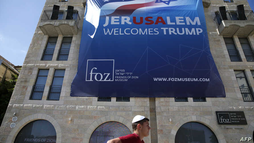 An Israeli youth walks past a poster welcoming and supporting US President Donald Trump in downtown Jerusalem, on May 19, 2017.