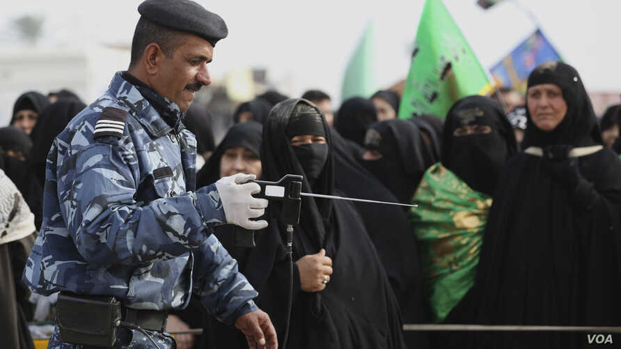 An Iraqi policeman uses a bomb detector to search Shi'ite pilgrims heading to the Shi'ite holy city of Karbala, 80 kilometers (50 miles) south of Baghdad, Iraq, Dec. 10, 2014.