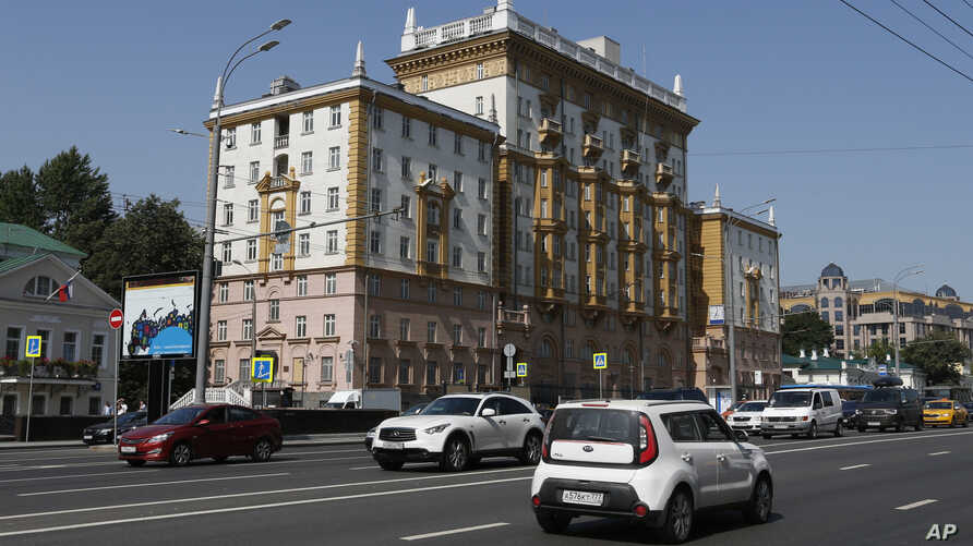 Vehicles drive past the U.S. Embassy in Moscow, Aug. 21, 2017.