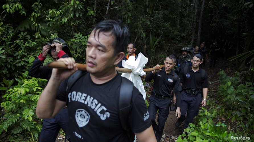 Members of a police forensic team carry a body bag with human remains dug from the grave near the abandoned human trafficking camp in the jungle close the Thailand border at Bukit Wang Burma in northern Malaysia May 27, 2015. Malaysian police forensi...