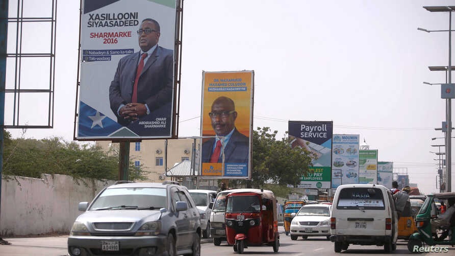 Motorists drive along a street with the campaign billboards of Somalia's Presidential candidates in Somalia's capital Mogadishu, Feb. 6, 2017.