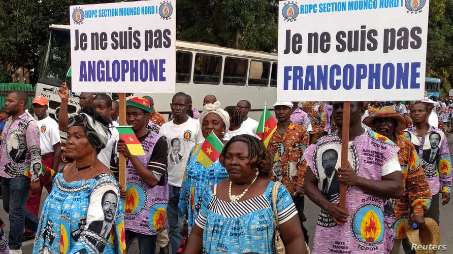 FILE - Demonstrators carry banners as they take part in a march voicing their opposition to independence or more autonomy for the anglophone regions, in Douala, Cameroon, Oct. 1, 2017.