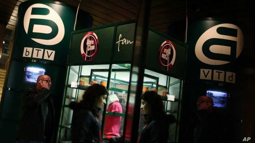 FILE - People walk past a fan shop of Bulgarian TV channel bTV in the capital Sofia, Thursday, Feb. 18, 2010.