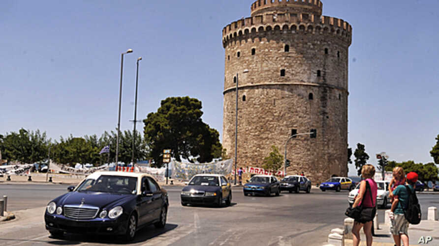 Striking taxi owners drive past the White Tower of Thessaloniki, the northern Greek city's main landmark, during a protest against certain austerity measures, as tourists look on, July 21, 2011