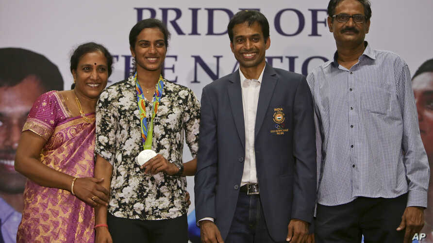 India's P.V. Sindhu, second left, who won one of India's two medals at the Rio de Janeiro Olympics poses with her coach Pullela Gopichand, second right, mother, P. Vijaya, left, and father, P.V. Ramana, right, during their reception at the Gopichand