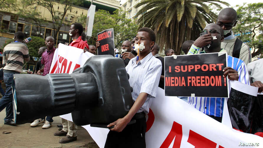 A Kenyan journalist carries a plastic replica of a camera as he participates in a protest along the streets of the capital Nairobi, Dec. 3, 2013.