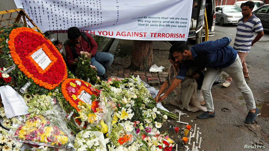 People place flowers at a makeshift memorial near the site, to pay tribute to the victims of the attack on the Holey Artisan Bakery and the O'Kitchen Restaurant, in Dhaka, Bangladesh, July 5, 2016. REUTERS/Adnan Abidi